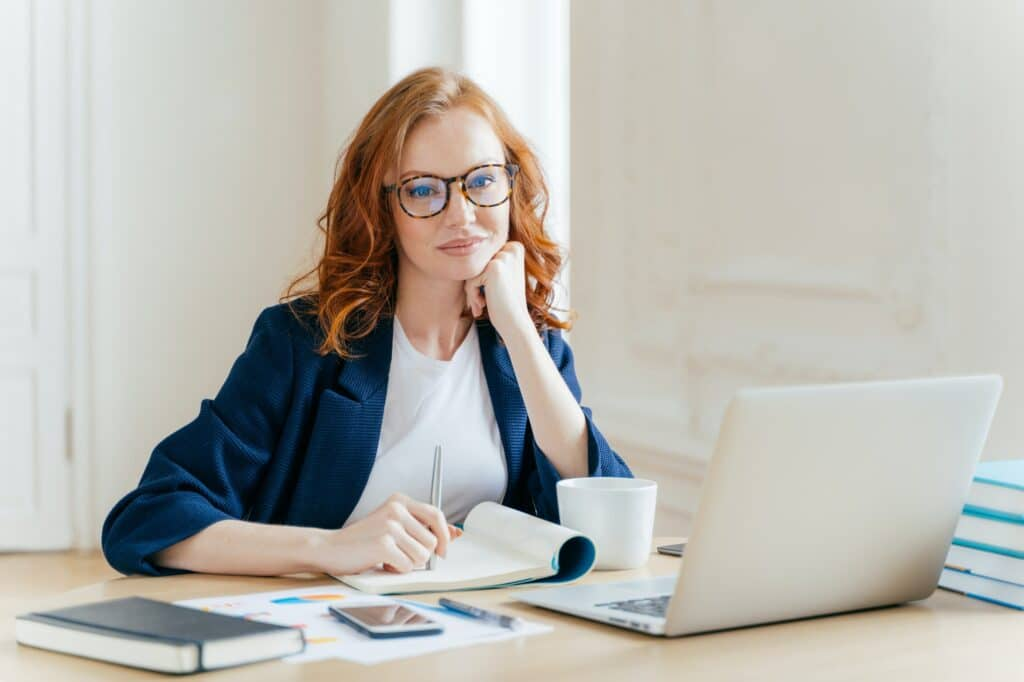 Redhead curly woman office worker analyzes data, makes accounting report, poses in office